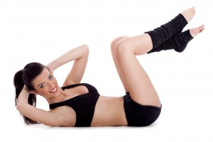 Fitness instructor doing situp exercise and turning to camera over white background